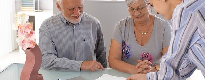 A smiling senior couple about to sign a form sitting at a desk with a young woman explaining to them