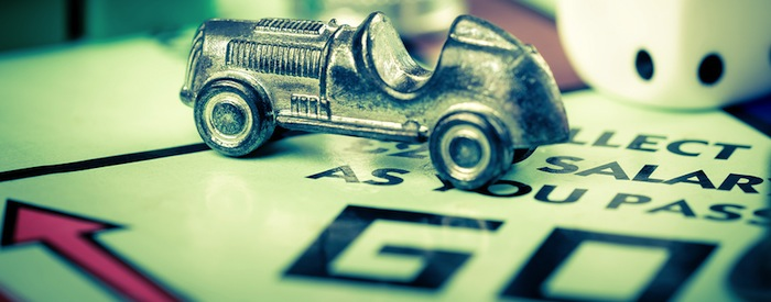 Close up of Monopoly game board with car token on the Go square