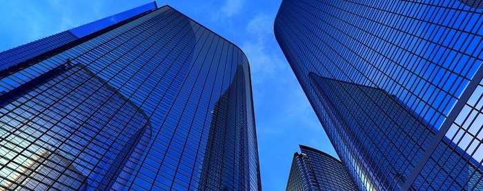Beautiful view from the ground up of modern reflective office buildings against a blue sky
