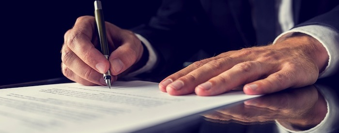 Close up of businessman's hands as he signs a document