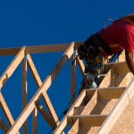 Carpenter with red shirt and white hardhat building a roof of a house at a construction site.