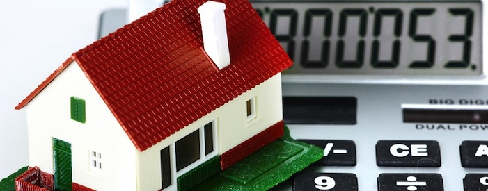 A miniature model of a house sitting on a calculator to represent taxes