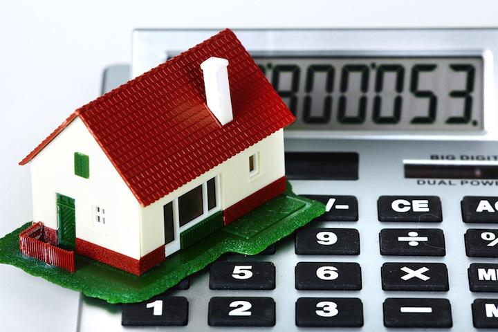 a small model house on a calculator to represent taxes conceptually