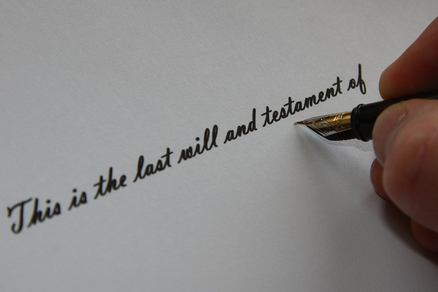 "hand holding a fountain pen writing the words ""the last will and testament of"""