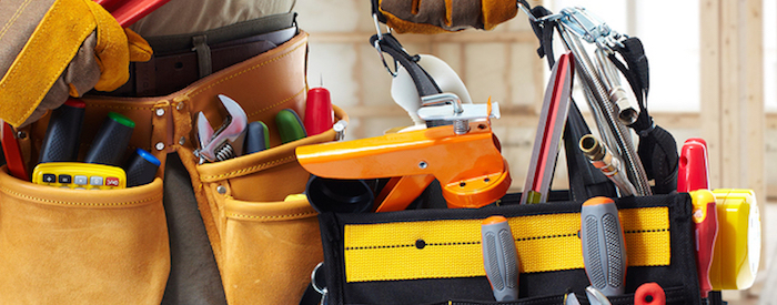 Close up of builder handyman with construction tools. House renovation background.